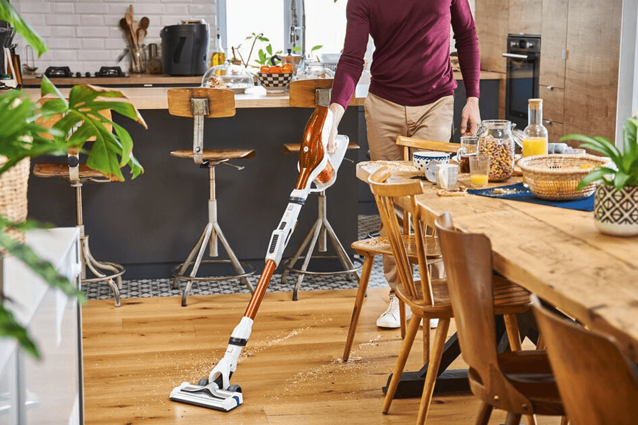 Man vacuuming in his kitchen